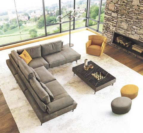 Picture of a living room with the Italian leather sectional in gray color. 2 small ottomans can be seen along with the accent chain in yellow. Black marble coffee table has a chess board on it. White carpet is seen, with the fire place in the background.