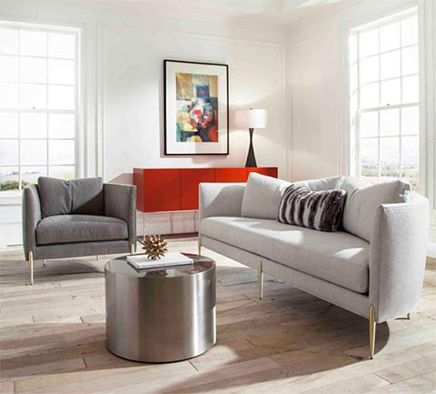 Sofas San Diego. A pictur of a modern living room with a sofa in light gray color. Dark gray chair is next to the sofa with a round metal coffe table in front. Red buffet table can be seen in the back with a picture on a wall.