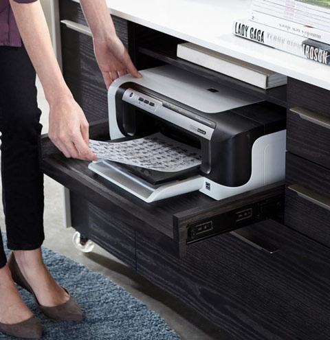 Cabinet with pullout drawwer for printer in charcoal color. A lady taking a paper from the printer.