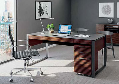 Modern office desk in wood with the metal frame. Office chair in light gray right next to it. Laptop and few objects show the modern office setting.