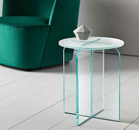 Modern end accent table in clear glass. Next to the table you can see a green accent chair.