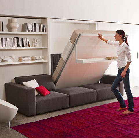 A young person easily lifting the wall bed. Modern room with a wall bed in brown with white shelves..